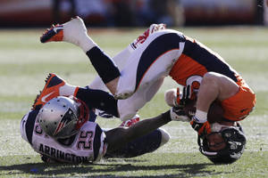 Photo - Denver Broncos wide receiver Wes Welker (83) is upended by New England Patriots cornerback Kyle Arrington (25) during the first half of the AFC Championship NFL playoff football game in Denver, Sunday, Jan. 19, 2014. (AP Photo/Julie Jacobson)