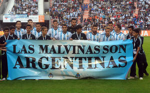 """Photo - Argentina's team poses for a picture with a banner reading in Spanish """"The Malvinas are Argentine"""" referring to the Malvinas Islands or the Falkland Islands before an international friendly soccer match against  Slovenia in La Plata, Argentina, Saturday, June 7, 2014.(AP Photo/Raul Ferrari- Telam)"""