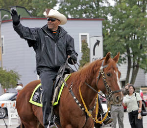 Photo - FILE - In this 2010 photo, Milwaukee County Sheriff David Clarke Jr. rides his horse during the Mexican Independence Day Parade in Milwaukee, Wis. The Wisconsin sheriff said he released an ad calling on residents to defend themselves because the old model of having a citizen call 911 and wait for help isn't always the best option. (AP Photo/Milwaukee Journal Sentinel, John Klein, file)