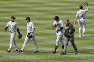 Photo - Chicago White Sox athletic trainer Herman Schneider, second from right, escorts Avisail Garcia (26) off the field after Garcia jammed his left shoulder on a diving catch during the sixth inning of a baseball game against the Colorado Rockies, Wednesday, April 9, 2014, in Denver. The Rockies won 10-4. (AP Photo/Barry Gutierrez)