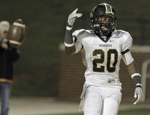 Photo - HIGH SCHOOL FOOTBALL: Midwest City's James Flanders (20) tosses a ball after scoring a touchdown during a game between Edmond Memorial and Midwest City at Wantland Stadium in Edmond, Thursday, Oct. 20, 2011.  Photo by Garett Fisbeck, The Oklahoman ORG XMIT: KOD