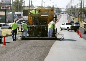 Photo - Crews do micro surfacing on S Pennsylvania Avenue between SW 44 and SW 59 in Oklahoma City on Friday. Micro surfacing extends the life of asphalt roadways and saves money. <strong>PAUL HELLSTERN - The Oklahoman</strong>
