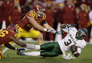 Photo -   Baylor wide receiver Lanear Sampson, right, is tackled by Iowa State defensive back Deon Broomfield, left, and linebacker Jake Knott (20) after making a reception during the first half of an NCAA college football game, Saturday, Oct. 27, 2012, in Ames, Iowa. Iowa State won 35-21. (AP Photo/Charlie Neibergall)
