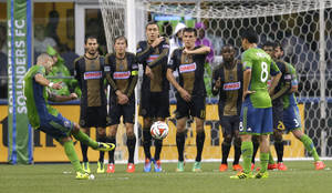 Photo - Philadelphia Union players make a wall as Seattle Sounders' Clint Dempsey, left, takes a penalty kick in the first half of an MLS soccer match, Saturday, May 3, 2014, in Seattle. The kick went wide to the right.(AP Photo/Ted S. Warren)