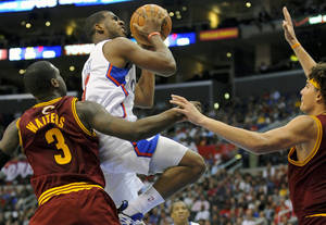 photo -   Cleveland Cavaliers guard Dion Waiters (3) and teammate center Anderson Varejao, right, double team Los Angeles Clippers guard Chris Paul as he drives to the basket in the second half of an NBA basketball game, Monday, Nov. 5, 2012, in Los Angeles. The Cavaliers won 108-101. (AP Photo/Gus Ruelas)  