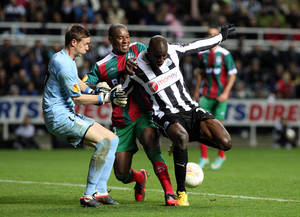 Photo -   Newcastle United's Demba Ba, right, has a shot on goal past Maritimo's goalkeeper Romain Salin, left, and Marcio Rosario, center, during their Europa League group D soccer match at St James' Park, Newcastle, England, Thursday, Nov. 22, 2012. (AP Photo/Scott Heppell)