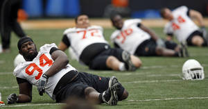 photo - The OSU Cowboys, including Anthony Rogers (94), stretch during Oklahoma State spring football practice at Boone Pickens Stadium in Stillwater, Okla., Monday, March 7, 2011. Photo by Nate Billings, The Oklahoman