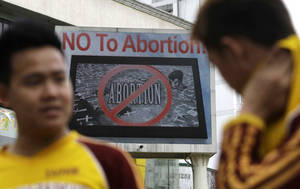 photo - An anti-abortion sign flashes on an electric signboard outside the Roman Catholic Minor Basilica of the Black Nazarene in downtown Manila, Philippines on Thursday, Jan. 3, 2013. Philippine President Benigno Aquino III last month signed the Responsible Parenthood and Reproductive Health Act of 2012. The law that provides state funding for contraceptives for the poor pitted the dominant Roman Catholic Church in an epic battle against the popular Aquino and his followers. (AP Photo/Aaron Favila)