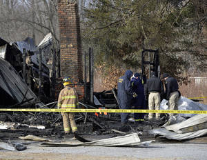 Photo - Kentucky State Fire investigators work at the scene of early morning house fire in Depoy, Ky. Thursday Jan. 30, 2014. As many as nine people were killed early Thursday in a house fire in rural western Kentucky and two people were taken to a hospital for treatment, officials said. Eleven people lived in the home in the Depoy community of Muhlenberg County, Greenville Assistant Fire Chief Roger Chandler said.  (AP Photo/Timothy D. Easley)