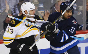 photo - Boston Bruins' Zdeno Chara (33) battles with Winnipeg Jets' Dustin Byfuglien (33) during the first period of their NHL hockey game, Sunday, Feb. 17, 2013, in Winnipeg, Manitoba. (AP Photo/The Canadian Press, Trevor Hagan)