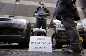 Photo - FILE - In this Wednesday, Feb. 26, 2014 file photo, Bitcoin trader Kolin Burges stands in protest outside an office building housing Mt. Gox in Tokyo. Bankrupt bitcoin exchange Mt. Gox said it found 200,000 bitcoins, which were previously thought stolen, in disused electronic wallets. Another 650,000 bitcoins still remain unaccounted for. (AP Photo/Shizuo Kambayashi, File)