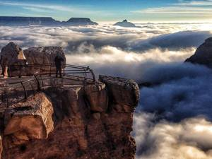 Photo - AP10ThingsToSee - In this photo released by the National Park Service, visitors to Mather Point at Grand Canyon National Park, Ariz. look out over a rare total cloud inversion, Friday Nov. 29, 2013. The phenomenon, caused by cold and warm air masses interacting, left the Grand Canyon peaking above a sea of clouds. (AP Photo/National Park Service, Erin Whittaker, File)