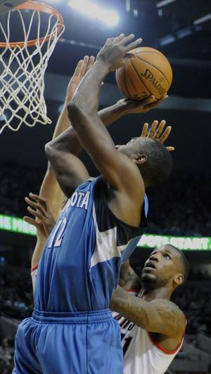 Photo - Minnesota Timberwolves' Luc Mbah a Moute (12) shoots against Portland Trail Blazers' Thomas Robinson (41) during the first half of an NBA basketball game in Portland, Ore., Sunday Feb. 23, 2014. (AP Photo/Greg Wahl-Stephens)