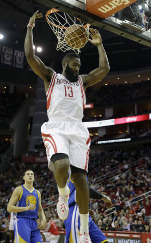 Photo - Houston Rockets' James Harden (13) dunks the ball against the Golden State Warriors during the fourth quarter of an NBA basketball game Friday, Dec. 6, 2013, in Houston. The Rockets won 105-83. (AP Photo/David J. Phillip)