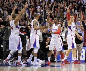 Photo - Los Angeles Clippers guard Randy Foye, left, celebrates as time runs out with teammates forward Caron Butler, third from left, guard Chris Paul, second from right, and forward Blake Griffin, right, as Portland Trail Blazers forward J.J. Hickson looks on in their NBA basketball game, Friday, March 30, 2012, in Los Angeles. The Clippers won 98-97.  (AP Photo/Mark J. Terrill)  ORG XMIT: LAS113