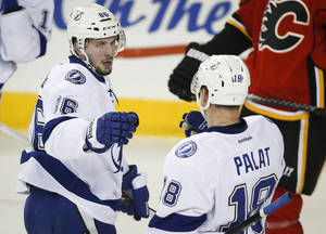 Photo - Tampa Bay Lightning's Nikita Kucherov, left, from Russia, celebrates his goal with teammate Ondrej Palat, from the Czech Republic, during the second period of an NHL hockey game against the Calgary Flames, Friday, Jan. 3, 2014, in Calgary, Alberta. (AP Photo/The Canadian Press, Jeff McIntosh)