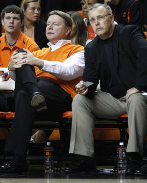 Photo - In this photo taken Nov. 9, 2011, Oklahoma State head coach Kurt Budke, left, sits on the bench next to associate head coach Jim Littell, right, during an exhibition college basketball game against Fort Hays State in Stillwater, Okla., Budke and assistant coach Miranda Serna were killed in a plane crash Thursday, Nov. 17, 2011, in Arkansas.  (AP Photo/Sue Ogrocki) <strong>Sue Ogrocki</strong>