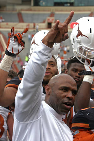 "Photo - Texas coach Charlie Strong gives the ""hook 'em horns"" sign while his players raise their helmets after the Orange and White spring NCAA college football game, Saturday, April 19, 2014, in Austin, Texas.  (AP Photo/Michael Thomas)"