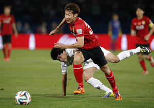 Photo - Guangzhou Evergrande's Yi Teng, center, tussles with Atletico Mineiro's Luan during the third place soccer match between Guangzhou Evergrande and Atletico Mineiro at the Club World Cup soccer tournament in Marrakech, Morocco, Saturday, Dec. 21, 2013. (AP Photo/Christophe Ena)