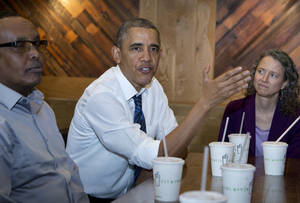 Photo - President Barack Obama flanked by Abdullahi Mohamed, left, and Meredith Upchurch speaks to reporters at a restaurant in Washington, Friday, May 16, 2014.  The president and Vice President Joe Biden met with construction workers involved in a recent infrastructure project.   (AP Photo/Manuel Balce Ceneta)