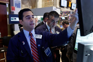 Photo - In this Monday, Dec. 16, 2013 photo, specialist William Geier, left, works on the floor of the New York Stock Exchange. Investors took to the sidelines Tuesday, Dec. 17, 2013, a day ahead of a key policy decision from the U.S. Federal Reserve that may see the central bank reduce its massive monetary stimulus. (AP Photo/Richard Drew)