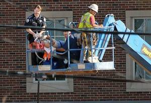 photo - Norman, Okla., fire personnel stablize a construction worker Monday, June 18, 2012 in Norman, Okla., as an aerial platform lowers them to the ground. The unidentified worker fell from the top of the four-story Headington Hall being constructed on the University of Oklahoma campus. The victim later died.  (AP Photo/The Norman Transcript,  Jerry Laizure)