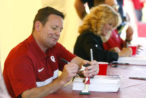 Photo - OU coaches Bob Stoops (left), Sherri Coale and Lon Kruger (top right) sign autographs during the Sooner Caravan at OU-Tulsa on Monday, May 6, 2013. MATT BARNARD/Tulsa World ORG XMIT: DTI1305062004281126