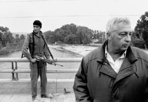 Photo - FILE - In this March 7, 1984 file photo, an Israeli soldier keeps his finger on the trigger of his assault rifle while Former Defense Minister Ariel Sharon, right, stands on the bridge overlooking the Awali River, Israel's most northerly position in Sidon, Lebanon. Sharon, the hard-charging Israeli general and prime minister who was admired and hated for his battlefield exploits and ambitions to reshape the Middle East, died Saturday, Jan. 11, 2014. The 85-year-old Sharon had been in a coma since a debilitating stroke eight years ago. (AP Photo/Max Nash, File)