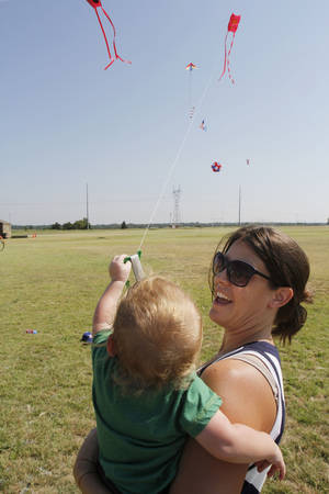 Photo - Tara Harwi and her 16-month-old son, Owen, enjoy flying a kite during KiteFest.