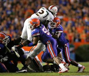 photo - Brandon  Spikes and Ryan Stamper stop Graig Cooper from getting a first down during the third quarter of the University of Florida vs University of Miami game at Florida Field Sept. 6, 2008. (  Brandon Kruse/The Gainesville Sun )