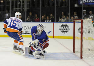Photo - New York Islanders' Cal Clutterbuck (15) shoots the puck past New York Rangers goalie Henrik Lundqvist to score a penalty goal in the first period of an NHL hockey game on Friday, Dec. 20, 2013, in New York. (AP Photo/Kathy Kmonicek)