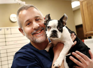 Photo - Tyler Mollet, second generation veterinarian, with Bernie, a Boston terrier,  in Mollet's Edmond clinic on Tuesday. <strong>Jim Beckel - THE OKLAHOMAN</strong>