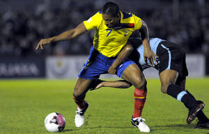 Photo -   Ecuador's Antonio Valencia, left, fights for the ball with Uruguay's Alvaro Pereira during a 2014 World Cup qualifying soccer game in Montevideo, Uruguay, Tuesday, Sept. 11, 2012. (AP Photo/Matilde Campodonico)