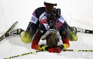 Photo - Germany's Franziska Preuss kneels on the snow after completing the women's biathlon 7.5k sprint, at the 2014 Winter Olympics, Sunday, Feb. 9, 2014, in Krasnaya Polyana, Russia. (AP Photo/Kirsty Wigglesworth)