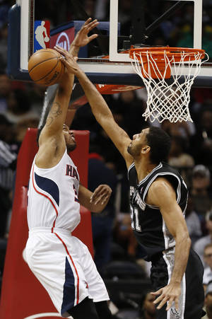 Photo - Atlanta Hawks power forward Mike Scott (32) has his shot blocked by San Antonio Spurs power forward Tim Duncan (21) in the first half of an NBA basketball game  Friday, Jan. 24, 2014, in Atlanta.  (AP Photo/John Bazemore)