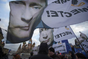 "Photo - People rally in support of Crimea joining Russia, with banners and portraits of Russian President Vladimir Putin, reading ""We are together,"" in Red Square in Moscow, Tuesday, March 18, 2014.  With a sweep of his pen, President Vladimir Putin added Crimea to the map of Russia on Tuesday, describing the move as correcting past injustice and responding to what he called Western encroachment upon Russia's vital interests. (AP Photo/Pavel Golovkin)"