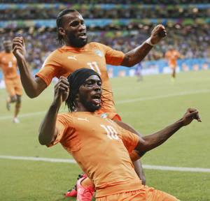 Photo - Ivory Coast's Gervinho (10) celebrates along with teammate Didier Drogba (11) after Gervinho scored his side's second goal during the group C World Cup soccer match between Ivory Coast and Japan at the Arena Pernambuco in Recife, Brazil, Saturday, June 14, 2014. (AP Photo/Petr David Josek)