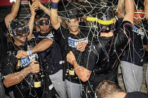 Photo - Tampa Bay Rays players celebrate in the clubhouse after beating the Cleveland Indians 4-0 in the AL wild-card baseball game Wednesday, Oct. 2, 2013, in Cleveland. The Rays advance to the AL division series against the Boston Red Sox. (AP Photo/Tony Dejak)