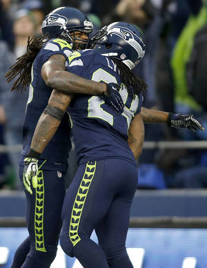 Photo - Seattle Seahawks running back Marshawn Lynch (24) is congratulated by wide receiver Sidney Rice after scoring on a 33-yard touchdown run against the Arizona Cardinals during the third quarter of an NFL football game in Seattle, Sunday, Dec. 9, 2012. (AP Photo/John Froschauer)
