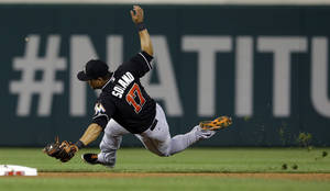 Photo - Miami Marlins second baseman Donovan Solano (17) fields a ball hit by Washington Nationals' Wilson Ramos but slips so Ramos was safe at first during the fourth inning of a baseball game at Nationals Park, Wednesday, Aug. 28, 2013, in Washington. (AP Photo/Alex Brandon)