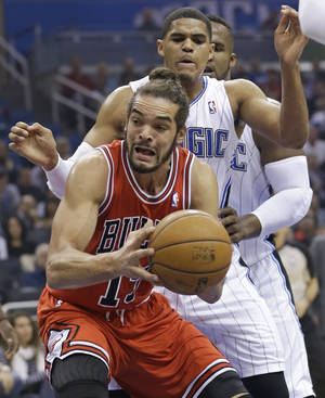 Photo - Chicago Bulls' Joakim Noah, front, looks to go up for a shot off a rebound in front of Orlando Magic's Tobias Harris during the first half of an NBA basketball game in Orlando, Fla., Wednesday, Jan. 15, 2014. (AP Photo/John Raoux)