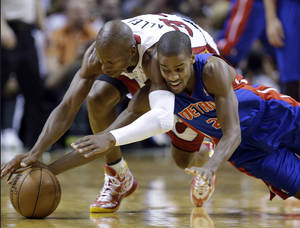 Photo - Detroit Pistons guard Kim English, right, and Miami Heat guard Ray Allen dive for a loose ball during the second half of an NBA basketball game, Friday, Jan. 25, 2013, in Miami. The Heat defeated the Pistons 110-88. (AP Photo/Wilfredo Lee)