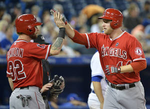 Photo - Los Angeles Angels' Mike Trumbo, right, celebrates his two-run home run with teammate Josh Hamilton, left, during second-inning AL baseball game action in Toronto, Wednesday, Sept. 11, 2013. (AP Photo/The Canadian Press, Nathan Denette)