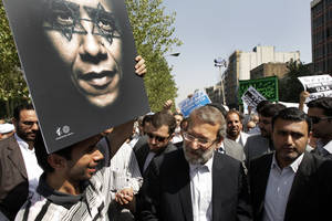 photo -   Iranian parliament speaker Ali Larijani, center, attends a protest after the Friday prayer, on Friday, Sept. 14, 2012, while a worshipper holds up a poster of US President Barack Obama, as part of widespread anger across the Muslim world about a film ridiculing Islam's Prophet Muhammad. (AP Photo/Vahid Salemi)
