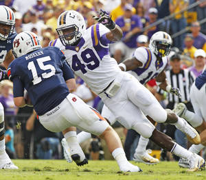 photo -   FILE - In this Oct. 22, 2011, file photo, LSU defensive end Barkevious Mingo (49) sacks Auburn quarterback Clint Moseley (15) during the first half of an NCAA college football game in Baton Rouge, La. A review of NFL rosters by STATS LLC shows 50 defensive linemen from the SEC _ 17 more than runner-up ACC. The SEC has reloaded with more NFL-ready talent this year, including LSU's Barkevious Mingo and Sam Montgomery, Auburn's Corey Lemonier, Georgia's John Jenkins and Alabama's Jesse Williams. (AP Photo/Bill Haber, File)