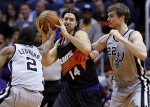 Photo - San Antonio Spurs' Kawhi Leonard (2) and Tiago Splitter (22), of Brazil, pressure Phoenix Suns' Luis Scola (14), of Argentina, during the first half of an NBA basketball game, Sunday, Feb. 24, 2013, in Phoenix. (AP Photo/Matt York)
