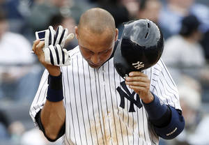 Photo - New York Yankees Derek Jeter reacts after striking out on a foul tip with two runners on base in the sixth inning of a baseball game against the Baltimore Orioles at Yankee Stadium in New York, Tuesday, April 8, 2014.  (AP Photo/Kathy Willens)