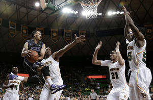 photo - TCU&#039;s Kyan Anderson (5) looks to pass as Baylor defenders Deuce Bello (14), Rico Gathers, Isaiah Austin (21) and Pierre Jackson (55) gather beneath the basket in the first half of an NCAA college basketball game Saturday, Jan. 12, 2013, in Waco, Texas. (AP Photo/Tony Gutierrez)