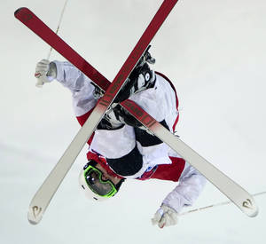 Photo - Canada's moguls skier Mikael Kingsbury flies over a jump during freestyle skiing training run at the 2014 Sochi Winter Olympics in Krasnaya Polyna, Russia, Wednesday, Feb. 5, 2014. (AP Photo/The Canadian Press, Jonathan Hayward)