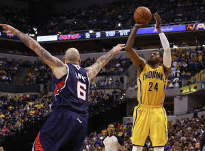 Photo - Indiana Pacers forward Paul George (24) shoots the basketball defended by Atlanta Hawks center Pero Antic in the second half of an NBA basketball game in Indianapolis, Sunday, April 6, 2014. Atlanta won 107-88.  (AP Photo/R Brent Smith)